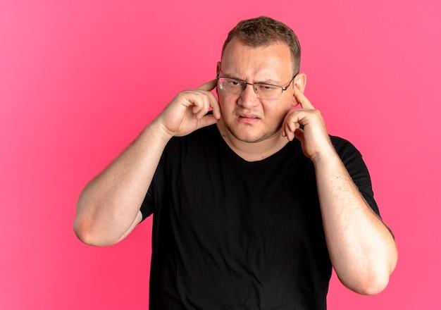 분홍색 위에 짜증이 난 표정으로 손가락으로 귀를 닫는 검은 티셔츠를 입고 안경에 과체중 남자