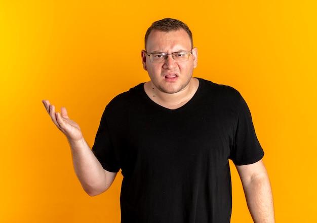 黒いtシャツを着た眼鏡をかけた太りすぎの男性は、オレンジ色について尋ねたり議論したりするように腕を伸ばして不満を持っています