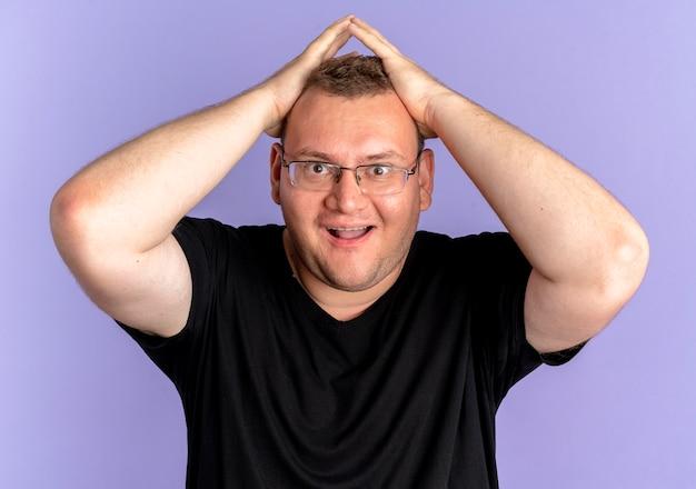 파란색 벽 위에 서있는 카메라를보고 행복하고 흥분된 검은 색 티셔츠를 입고 안경에 과체중 남자