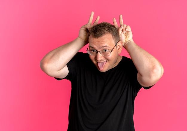 ピンクの壁の上に立っている舌を突き出してバニーの耳を模倣して楽しんでいる黒いtシャツを着て眼鏡をかけた太りすぎの男
