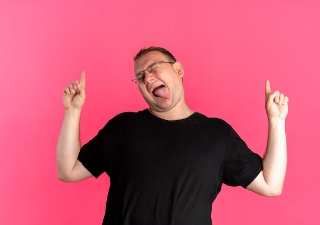 ピンクの壁の上に立っている人差し指で上向きに舌を突き出して楽しんでいる黒いtシャツを着て眼鏡をかけた太りすぎの男