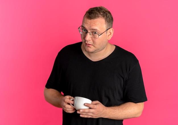 커피 컵을 들고 검은 티셔츠를 입고 안경에 중량이 초과 된 남자는 분홍색 벽 위에 서 혼란