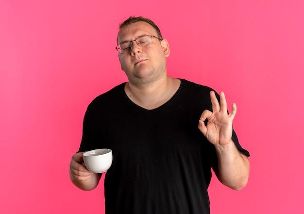 확인 표시를 하 고 커피 컵을 들고 검은 티셔츠를 입고 안경에 중량이 초과 된 남자는 분홍색 벽 위에 서 기쁘게