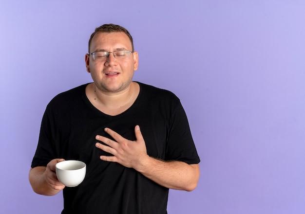青い壁の上に立って感謝を感じて胸に手をつないでコーヒーカップを保持している黒いtシャツを着て眼鏡をかけた太りすぎの男