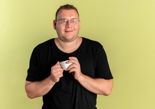 가벼운 벽 위에 감정적이고 행복하게 서있는 커피 컵을 들고 검은 티셔츠를 입고 안경에 과체중 남자