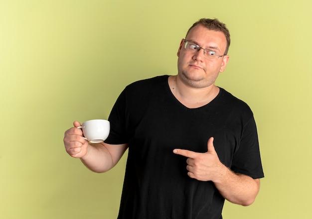 손가락으로 가리키는 커피 컵을 들고 검은 티셔츠를 입고 안경에 중량이 초과 된 남자가 옆으로 가벼운 벽에 서서 혼란스러워합니다.