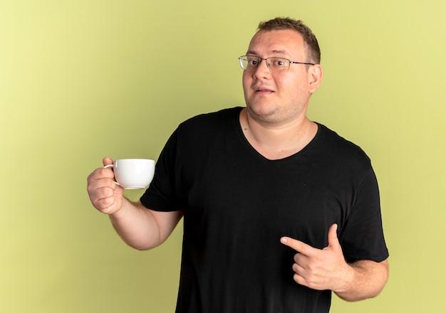 明るい壁の上に立っている幸せそうな顔でそれを指で指しているコーヒーカップを保持している黒いtシャツを着て眼鏡をかけた太りすぎの男