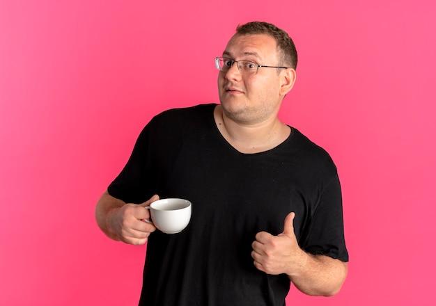 ピンクの上に笑みを浮かべて親指を示すコーヒーカップを保持している黒いtシャツを着て眼鏡をかけた太りすぎの男