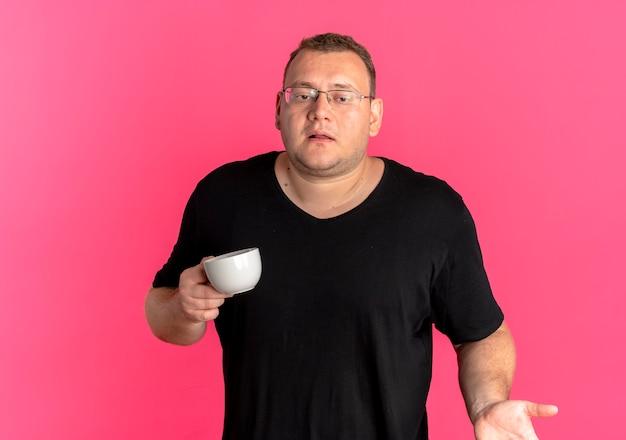 분홍색 벽 위에 서있는 혼란 스 러 워 보이는 어깨를 shrugging 커피 컵을 들고 검은 티셔츠를 입고 안경에 과체중 남자