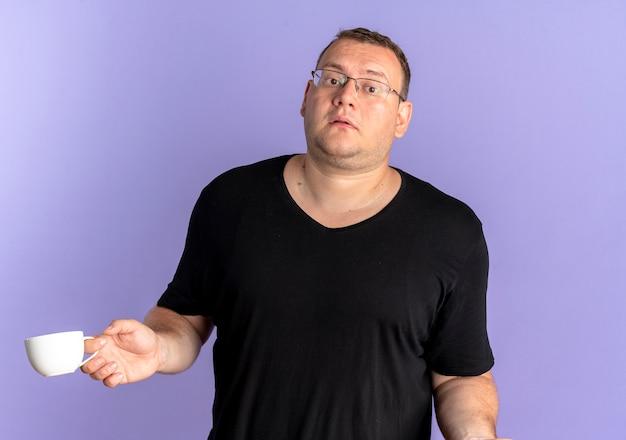 青で混乱しているように見えるコーヒーのカップを保持している黒いtシャツを着て眼鏡をかけた太りすぎの男