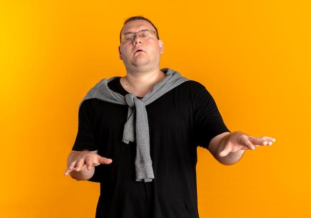 オレンジ色の壁の上に立って目を閉じて手を差し伸べる黒いtシャツを着た眼鏡の太りすぎの男