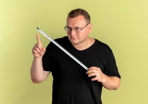 明るい壁の上に立っている深刻な顔でそれを見てメジャーテープを保持している黒いtシャツを着て眼鏡をかけた太りすぎの男