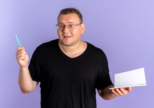 파란색 위에 혼란 스 러 워 노트북과 펜을 들고 검은 티셔츠를 입고 안경에 중량이 초과 된 남자