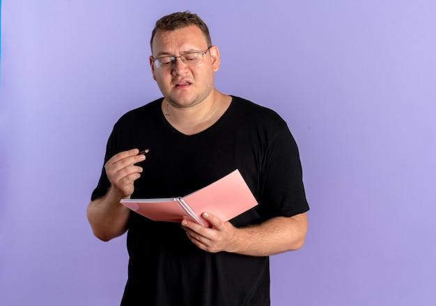 노트북과 펜을 들고 검은 티셔츠를 입고 안경에 중량이 초과 된 남자는 파란색 벽 위에 서 혼란 스 러 워 찾고
