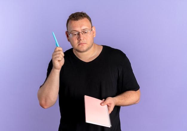 노트북과 펜을 들고 검은 티셔츠를 입고 안경에 중량이 초과 된 남자는 파란색 벽 위에 의아해 서 찾고