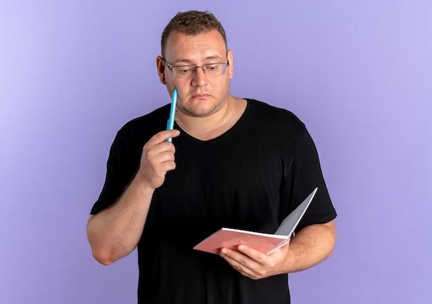 파란색 벽 위에 서 잠겨있는 표정으로 찾고 노트북과 펜을 들고 검은 티셔츠를 입고 안경에 과체중 남자