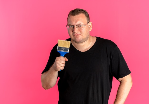 ペイントブラシを保持している黒いtシャツを着て眼鏡をかけている太りすぎの男性は、ピンクに混乱して不満を持っています