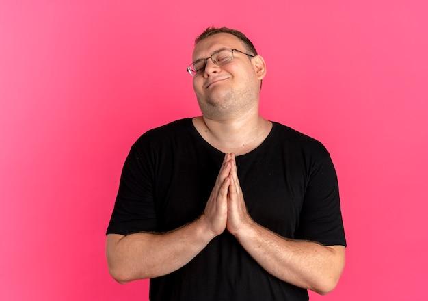 ピンクの上に幸せそうな顔で祈るように手のひらを一緒に保持している黒いtシャツを着て眼鏡をかけた太りすぎの男