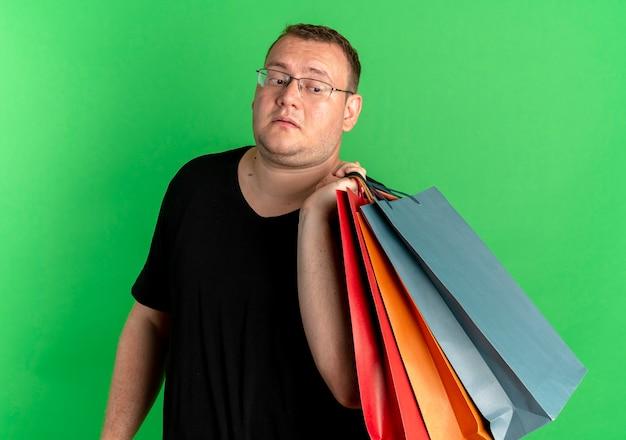 녹색 위에 혼란 스 러 워 보이는 종이 가방을 들고 검은 티셔츠를 입고 안경에 중량이 초과 된 남자