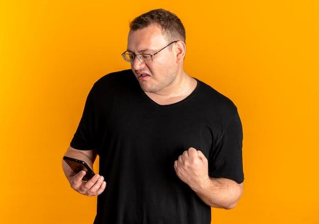 오렌지 위에 행복하고 흥분된 주먹 떨림 스마트 폰 들고 검은 티셔츠를 입고 안경에 과체중 남자