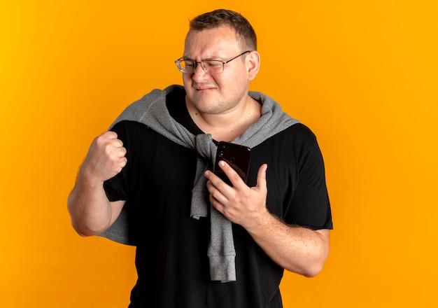 오렌지 벽 위에 서 행복하고 흥분된 주먹 떨림 스마트 폰 들고 검은 티셔츠를 입고 안경에 과체중 남자