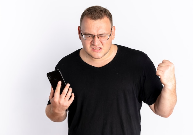 흰 벽 위에 서있는 성난 얼굴로 주먹을 떨리는 스마트 폰을 들고 검은 티셔츠를 입고 안경에 과체중 남자