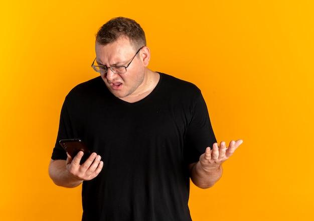 Полный мужчина в очках в черной футболке держит смартфон, глядя на экран с растерянным выражением лица, стоя над оранжевой стеной