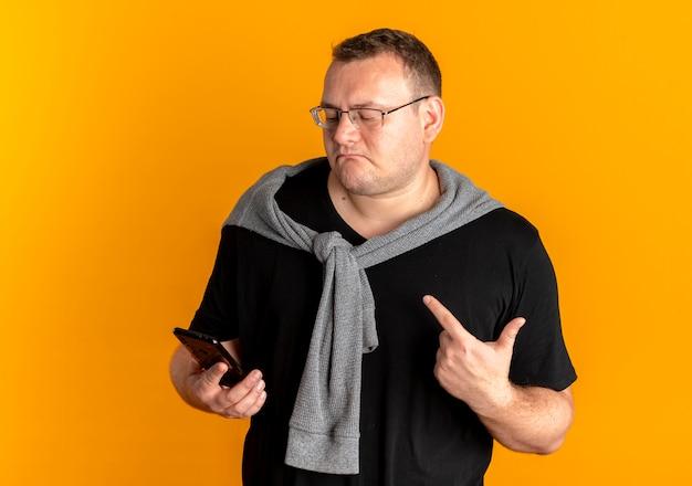 オレンジ色の壁の上に立っている人差し指を見せて不機嫌そうに見えるスマートフォンを保持している黒いtシャツを着て眼鏡をかけた太りすぎの男