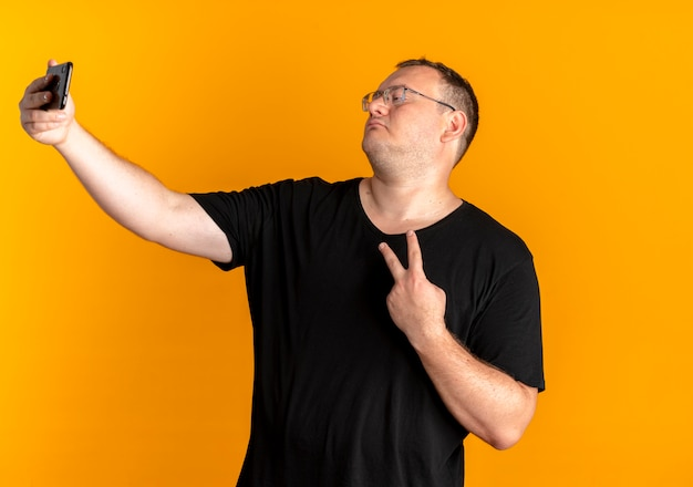 オレンジ色の壁の上に立っている勝利のサインを示すselfieを作るスマートフォンを保持している黒いtシャツを着て眼鏡をかけた太りすぎの男