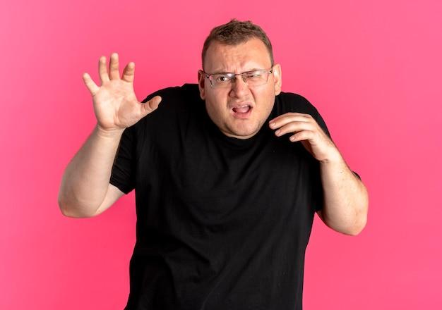 Полный мужчина в очках в черной футболке смотрит в камеру с выражением страха, делая защитный жест руками над розовым