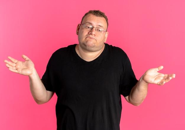 黒のtシャツを着た眼鏡をかけた太りすぎの男性は、ピンクの壁の上に立っている答えがない側に腕を広げて混乱しました