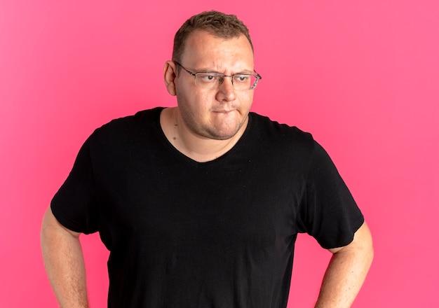 ピンクの上に困惑して脇を見て黒いtシャツを着て眼鏡をかけた太りすぎの男