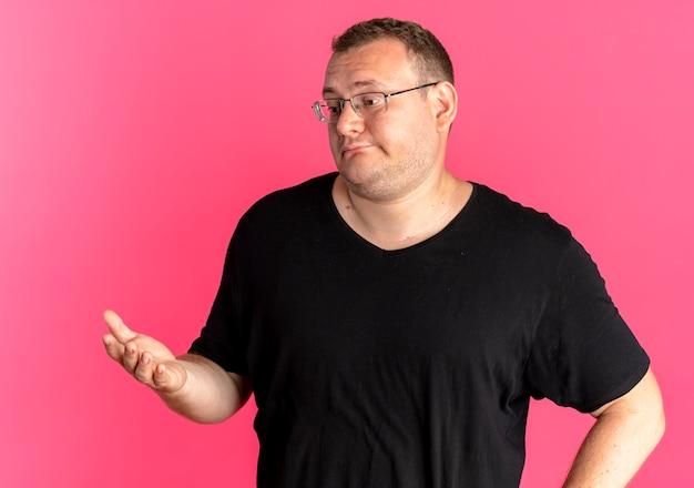 Полный мужчина в очках в черной футболке смотрит в сторону с вытянутой рукой, думает или спрашивает, стоя над розовой стеной