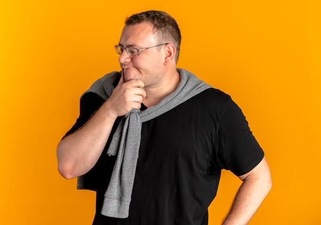 주황색 벽 위에 서있는 잠겨있는 표정으로 턱에 손으로 제쳐두고 찾고 검은 티셔츠를 입고 안경에 과체중 남자