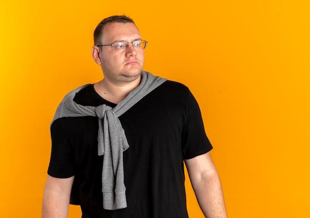 오렌지 위에 심각한 자신감 표정으로 옆으로 찾고 검은 티셔츠를 입고 안경에 과체중 남자