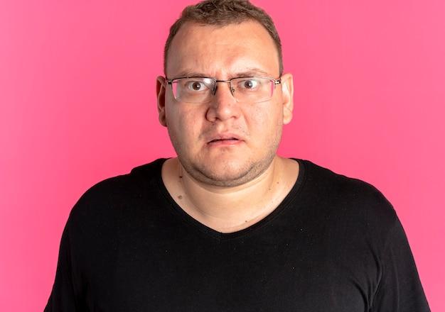 카메라를보고 검은 티셔츠를 입고 안경에 중량이 초과 된 남자가 놀랍고 분홍색 벽 위에 서서 불쾌감을 느낍니다.