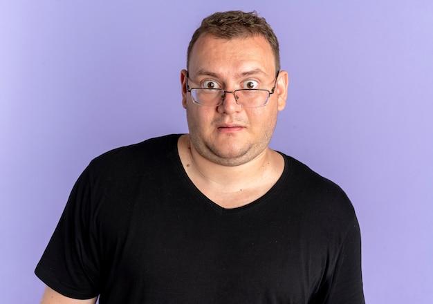 카메라를보고 검은 티셔츠를 입고 안경에 중량이 초과 된 남자가 파란색 벽 위에 서 놀란