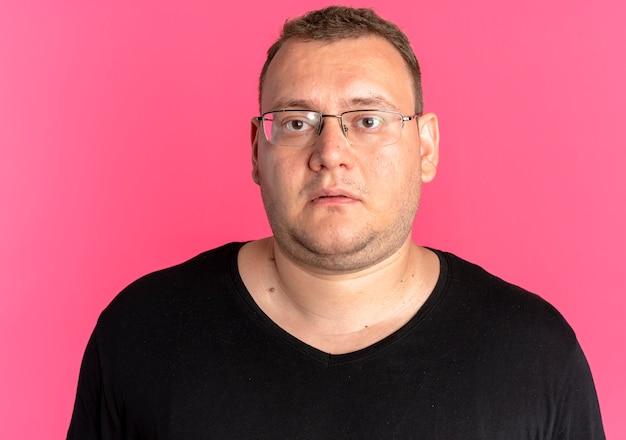 분홍색 벽 위에 서있는 슬픈 표정으로 카메라를보고 검은 티셔츠를 입고 안경에 과체중 남자