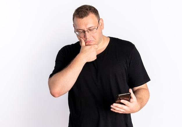 그의 스마트 폰 화면을보고 검은 티셔츠를 입고 안경에 과체중 남자는 흰 벽 위에 서 의아해
