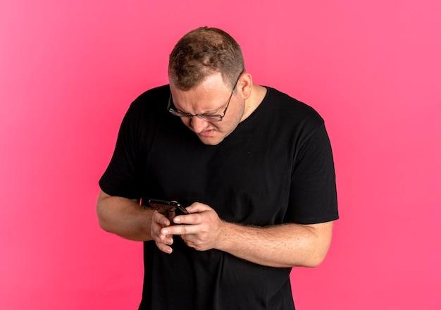 Полный мужчина в очках в черной футболке смотрит на экран смартфона с сердитым лицом поверх розового