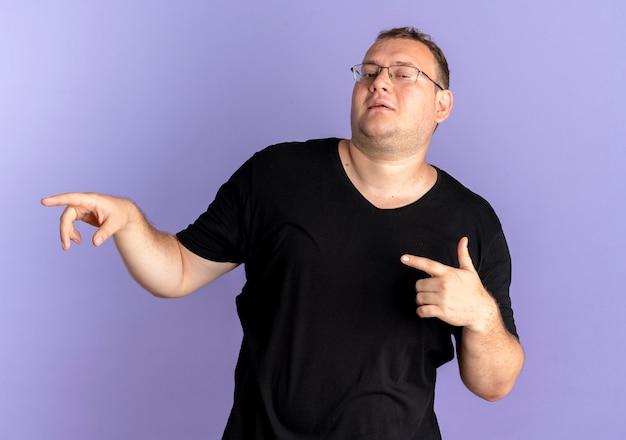 眼鏡をかけた太りすぎの男性が、青い上に人差し指で自信を持って尖った黒いtシャツを着ています。