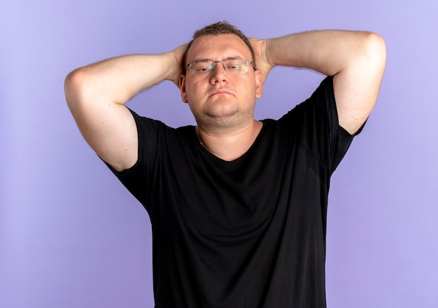 파란색 위에 그의 머리에 손으로 자신감을 찾고 검은 티셔츠를 입고 안경에 과체중 남자