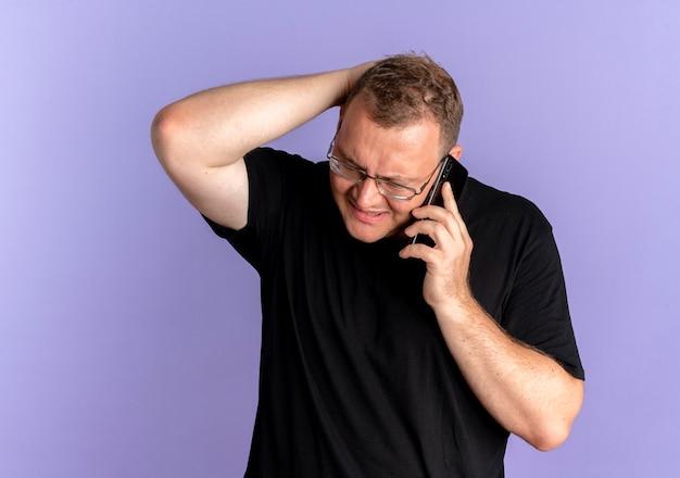 파란색을 통해 휴대 전화로 이야기하는 동안 혼란스럽고 불쾌한 검은 티셔츠를 입고 안경에 과체중 남자