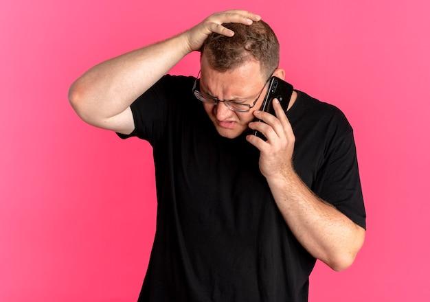 분홍색을 통해 휴대 전화로 이야기하는 동안 혼란스럽고 불쾌한 검은 티셔츠를 입은 안경에 과체중 남자