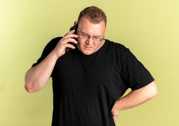 가벼운 벽 위에 서있는 휴대 전화로 이야기하면서 혼란스럽고 불쾌한 검은 색 티셔츠를 입은 안경에 과체중 남자