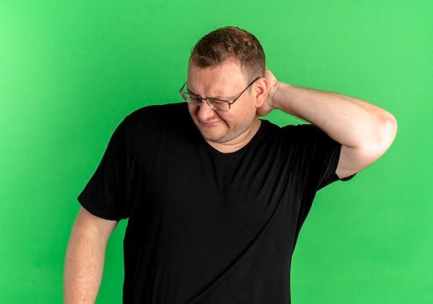 녹색 위에 혼란스럽고 의아해 보이는 검은 티셔츠를 입고 안경에 과체중 남자