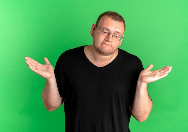 緑の壁の上に立っている答えがない側に混乱して不確かな広がりの腕を探している黒いtシャツを着ている眼鏡の太りすぎの男