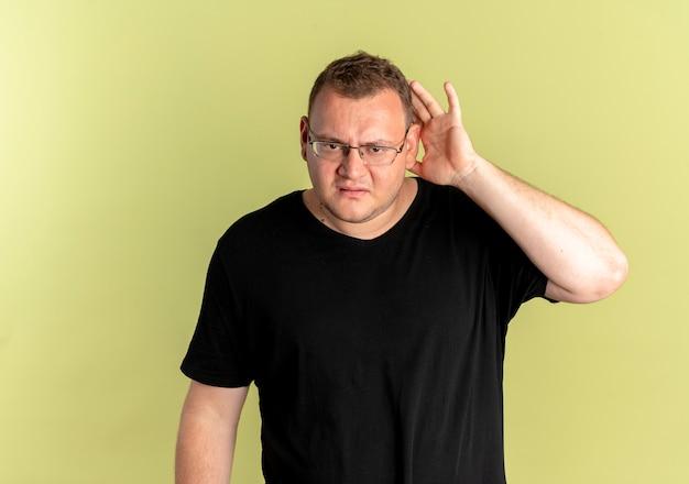 검은 색 티셔츠를 입고 안경에 과체중 남자가 가벼운 벽 위에 서서 듣고 싶어하는 귀 근처에 손바닥을 들고 혼란스러워하고 있습니다.
