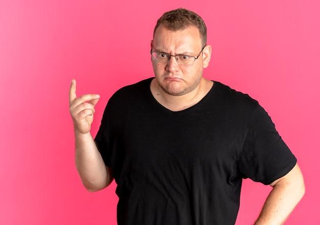ピンクの壁の上に立っている人差し指の思考を示して混乱しているように見える黒いtシャツを着て眼鏡をかけた太りすぎの男