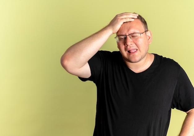 明るい壁の上に立っている間違いのために彼の頭の上の手と混同しているように見える黒いtシャツを着た眼鏡の太りすぎの男